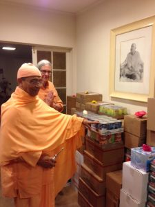 Pravrajika Saradeshaprana looks on as Swami Sarvadevananda blesses food offerings.